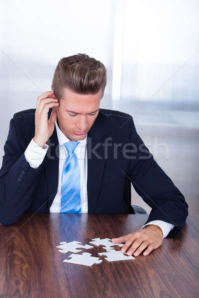 Businessman Holding Jigsaw Puzzle Stock photo © AndreyPopov