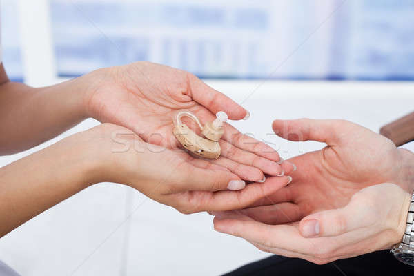 Doctor Giving Hearing Aid To Male Patient Stock photo © AndreyPopov