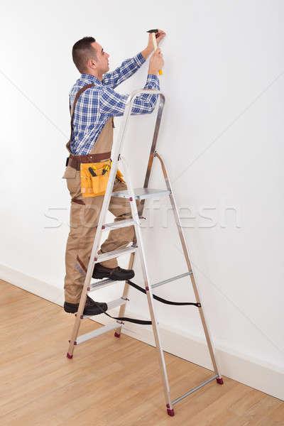 Muur nagel jonge mannelijke ladder Stockfoto © AndreyPopov
