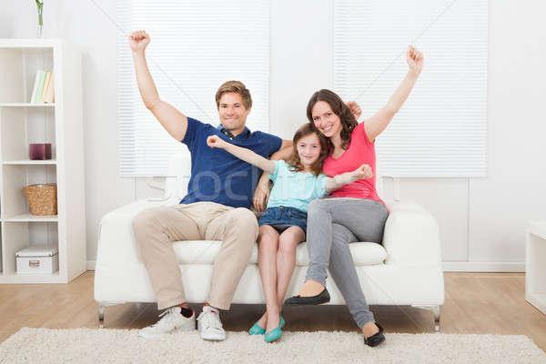 Derűs család karok a magasban ül kanapé teljes alakos Stock fotó © AndreyPopov