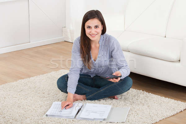 Woman Calculating Home Finances On Rug Stock photo © AndreyPopov