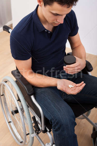 Man Holding Medicine While Sitting On Wheelchair Stock photo © AndreyPopov