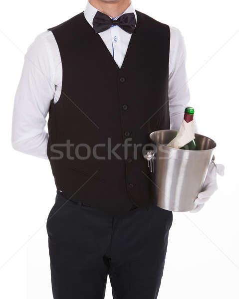 Waiter Holding Champagne Bottle In Cooler Stock photo © AndreyPopov