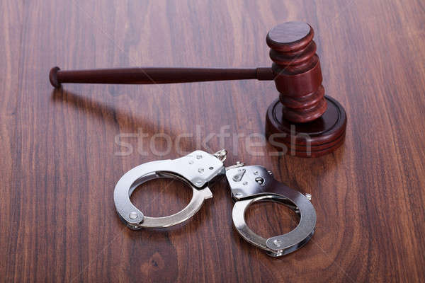 Gavel And Handcuffs On Wooden Table Stock photo © AndreyPopov