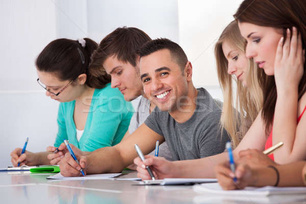 Handsome Student Sitting With Classmates Writing At Desk Stock photo © AndreyPopov