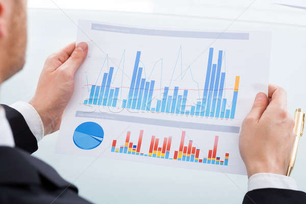 Businessman Comparing Graphs At Office Desk Stock photo © AndreyPopov