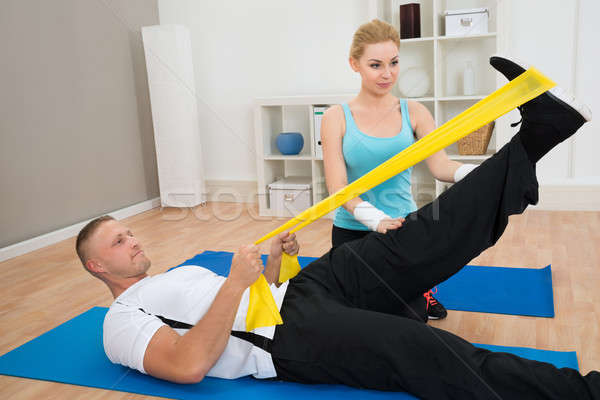 Female Instructor Helping Young Man While Exercising Stock photo © AndreyPopov