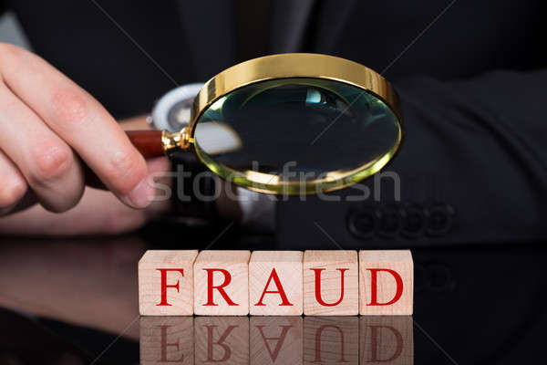 Businessman Examining Fraud Blocks Through Magnifying Glass Stock photo © AndreyPopov