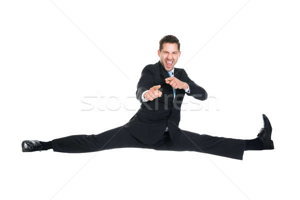 Businessman Doing Splits While Gesturing Over White Background Stock photo © AndreyPopov
