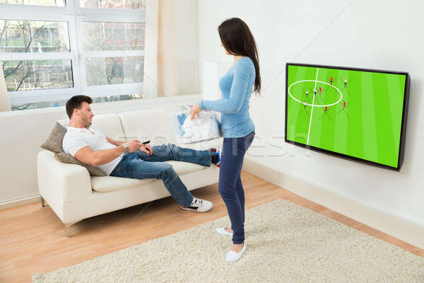 Woman Looking At Man Watching Football Match On Television Stock photo © AndreyPopov