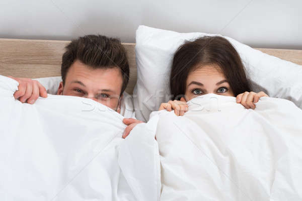 Young Couple Peeking From Bedsheets Stock photo © AndreyPopov