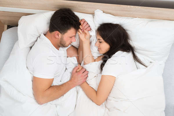Stock photo: Couple Holding Hands Sleeping On Bed