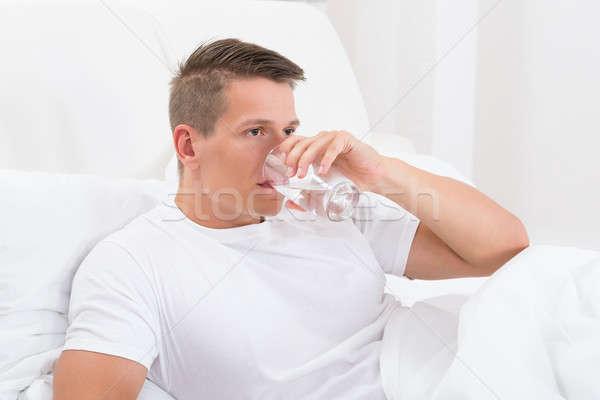 Fiatalember ivóvíz ül ágy víz otthon Stock fotó © AndreyPopov