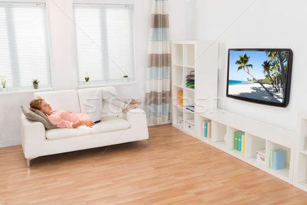 Fiatal nő tv nézés kanapé otthon ház televízió Stock fotó © AndreyPopov