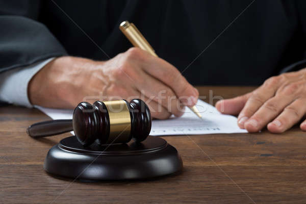 Judge Writing On Paper In Courtroom Stock photo © AndreyPopov