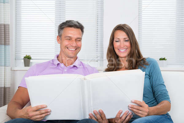 Mature Couple Looking At Photo Album Stock photo © AndreyPopov