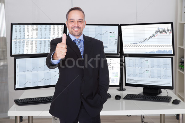 Broker Gesturing Thumbs Up Against Multiple Monitors Stock photo © AndreyPopov