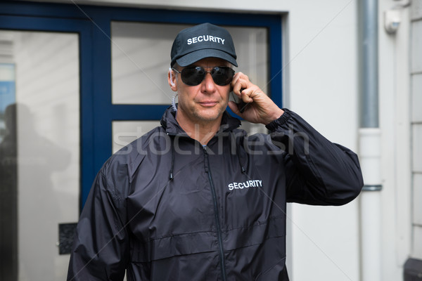 Stock photo: Confident Security Guard Using Mobile Phone Outside Building