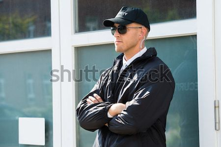 Security Guard Using Mobile Phone Outside Building Stock photo © AndreyPopov