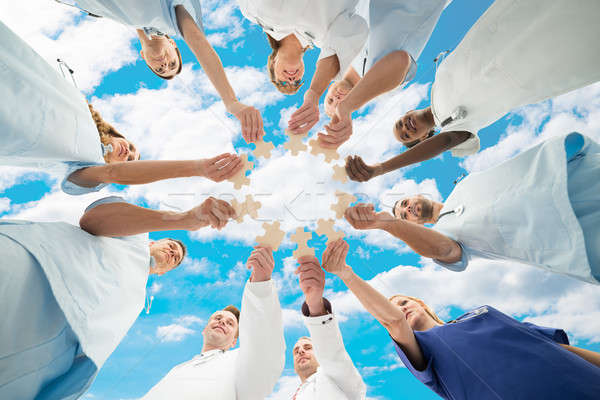 Medical Team Joining Jigsaw Pieces Against Sky Stock photo © AndreyPopov