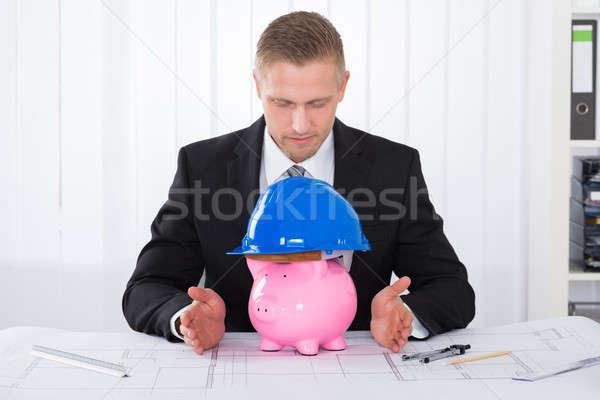 Male Architect With Piggybank Wearing Construction Helmet Stock photo © AndreyPopov