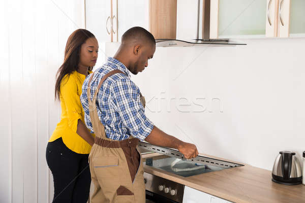 Stock photo: Serviceman Repairing Stove