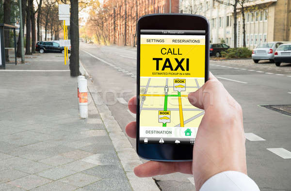 Person's Hand Booking Taxi On Smart Phone Stock photo © AndreyPopov