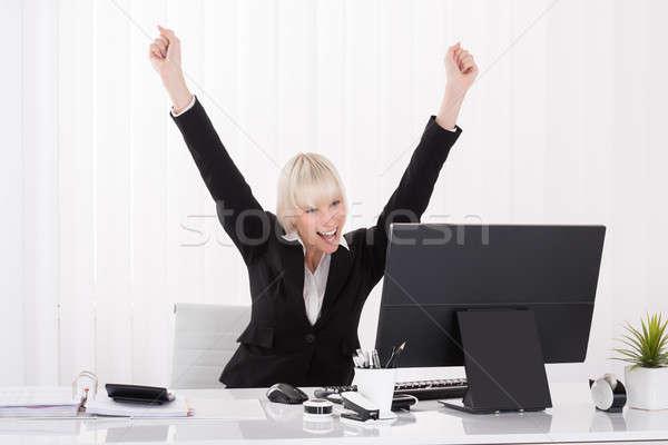 Happy Businesswoman Raising Arms At Desk Stock photo © AndreyPopov