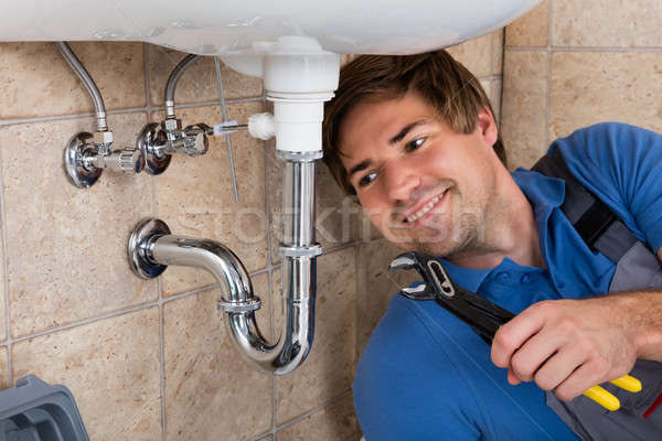 Male Plumber Repairing Sink In Bathroom Stock photo © AndreyPopov