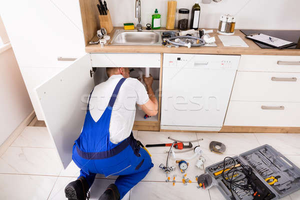 Plumber In Overall Repairing Sink Pipe Stock photo © AndreyPopov