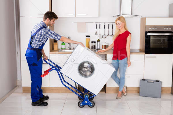 Male Worker Using Hand Truck For Carrying Washer In Kitchen Stock photo © AndreyPopov