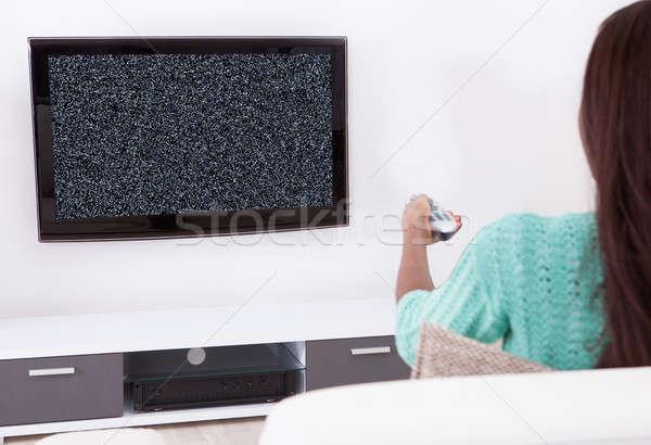 Kobieta oglądanie telewizji nie sygnał posiedzenia Zdjęcia stock © AndreyPopov