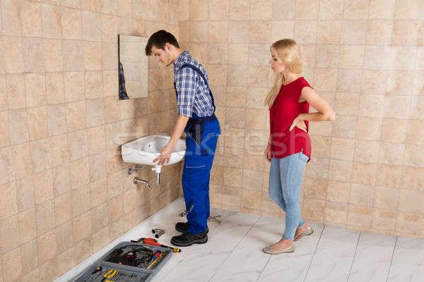 Young Handyman Installing Sink In Bathroom Stock photo © AndreyPopov