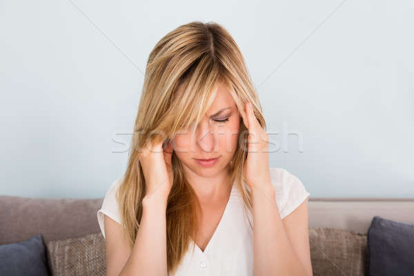 Stock photo: Woman Suffering From Headache At Home
