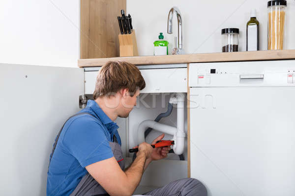 Stock photo: Male Plumber Fixing Sink Pipe