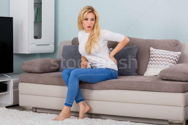 Donna sofferenza mal di schiena seduta divano Foto d'archivio © AndreyPopov