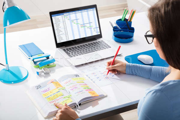 Businesswoman Marking Schedule On Calendar With Red Marker Stock photo © AndreyPopov