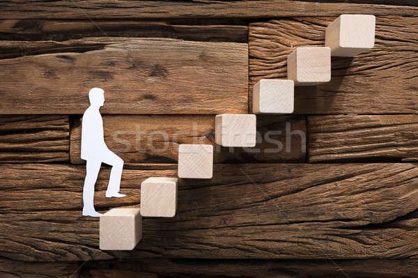 Paper Businessman Climbing Block Ladder On Wood Stock photo © AndreyPopov