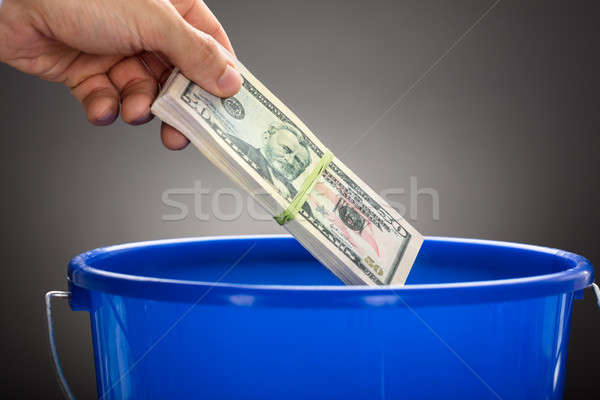 Hand Throwing Us Paper Currency Bundle In Blue Bucket Stock photo © AndreyPopov