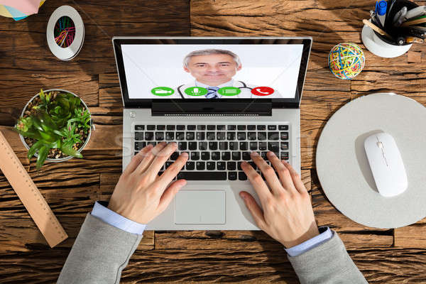 Elevated View Of A Businessperson Video Conferencing With Doctor Stock photo © AndreyPopov