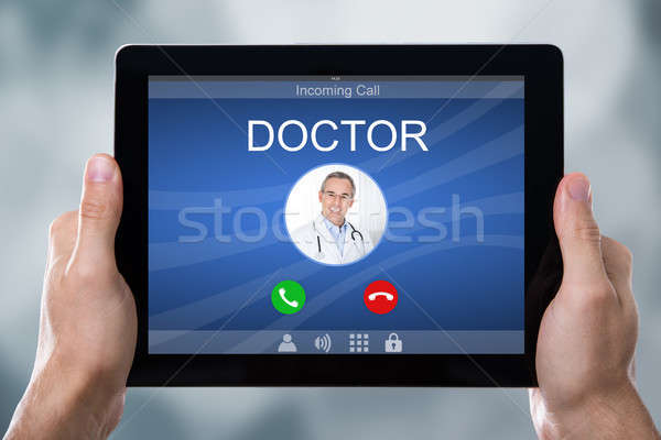 Person's Hand Holding Tablet With Doctor's Incoming Call Stock photo © AndreyPopov