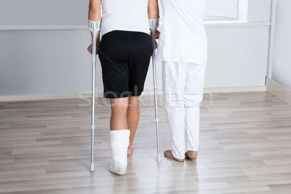 Pomoc ranny człowiek chodzić kule kalekiego kobiet Zdjęcia stock © AndreyPopov