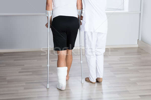 Ayudar herido hombre caminata muletas femenino Foto stock © AndreyPopov
