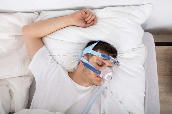 Man Lying On Bed With Sleeping Apnea And CPAP Machine Stock photo © AndreyPopov