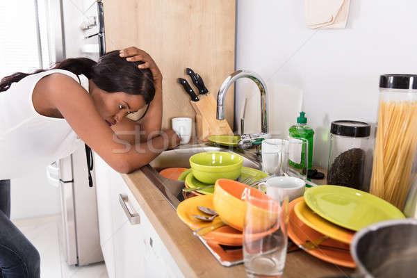 Hangsúlyos nő dől mosogató néz kellékek Stock fotó © AndreyPopov