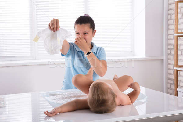 Woman Changing Stinky Diaper Of Her Baby Stock photo © AndreyPopov
