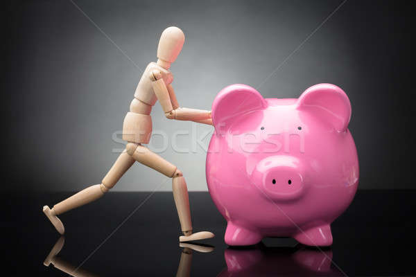 Wooden Dummy Holding Piggy Bank Stock photo © AndreyPopov