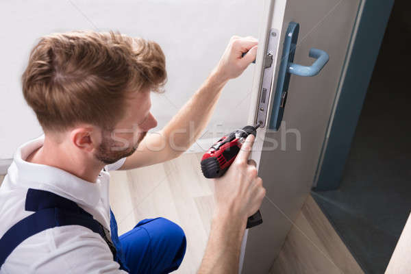 Young Carpenter Install Door Lock Stock photo © AndreyPopov