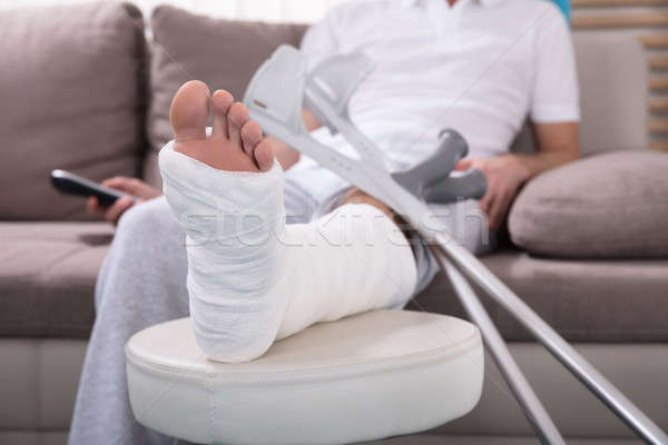 Hombre fractura en la pierna sesión sofá joven Foto stock © AndreyPopov