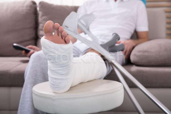 Homme jambe cassée séance canapé jeune homme Photo stock © AndreyPopov